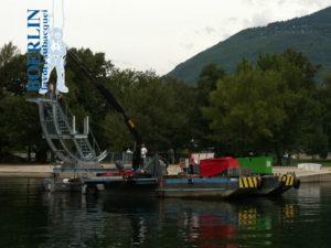 """Abriss des alten Trampolins in der Freizeitanlage """"Lido Patriziale"""", Ascona. Einschlagen von 4 Metallpfählen (10 m x 30 cm) in den Grund, Aufbau und Aufstellung des neuen Trampolins."""